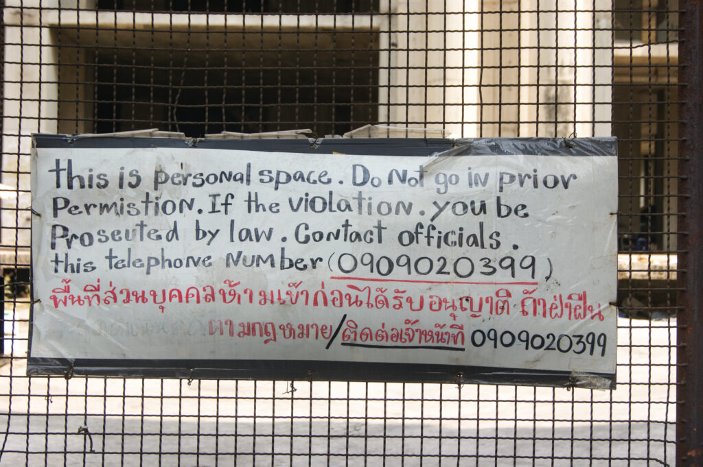 """Sign on fence reading in broken English: """"this is personal space. Do not go in prior permistion. If the violation you be proseuted by law. Contact officials this telephone number (0909020399)"""""""